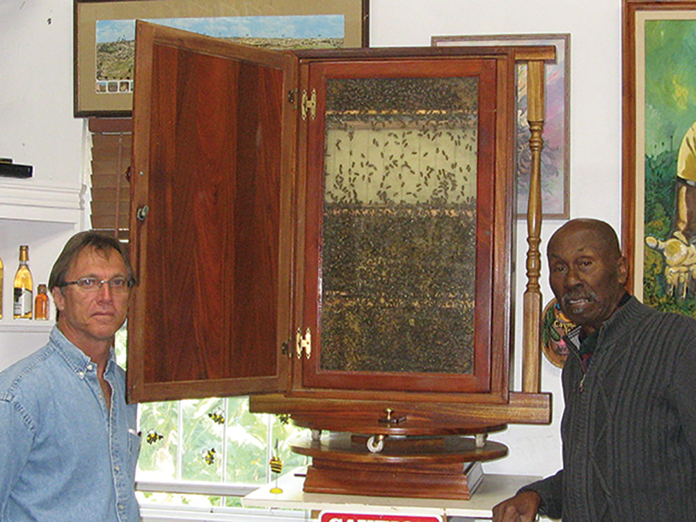 """Randolph Furbert (on right) is one of Bermuda's best known beekeepers and runs one of the island's largest operations, Chartwell Apiaries. Mr. Furbert is pictured here in an office in the back of his honey house with the President of the Bermuda Beekeeper's Association, Tommy Sinclair and a beautiful observation hive."""""""