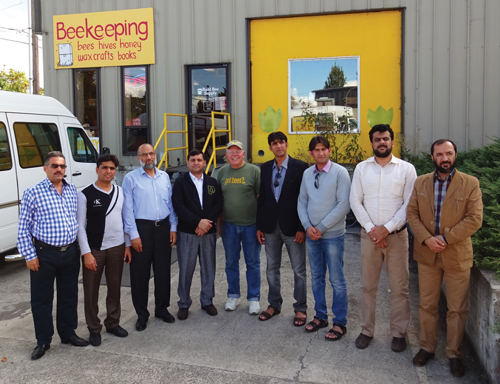 Dewey, center, with Afghani visitors at Ruhl Beekeeping Supply Store.