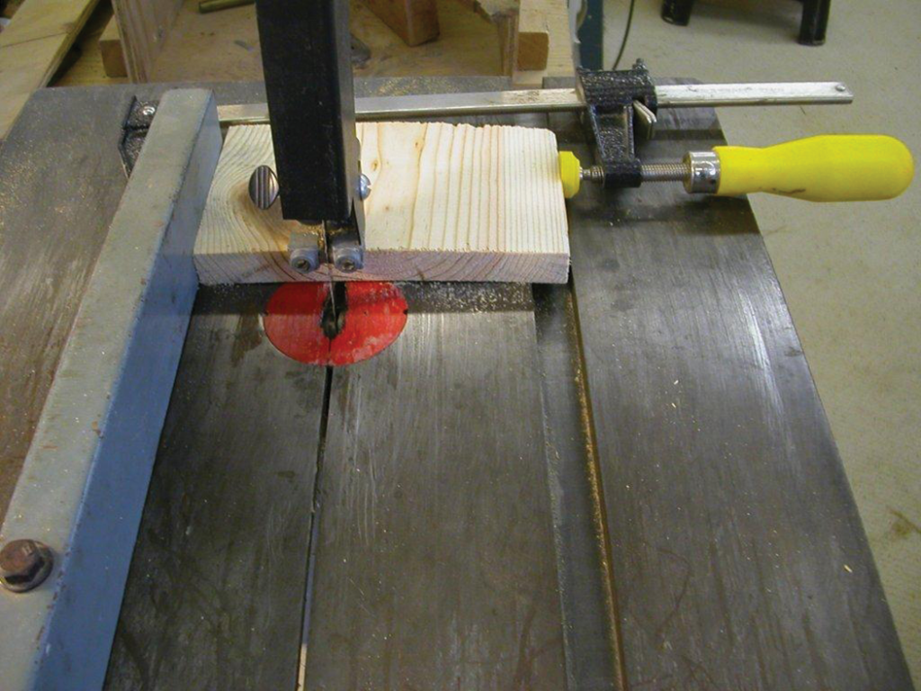 With the band saw fence set, add a stop block to preclude cutting too deep into the sides.