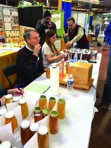From top, Perry Arlia, brings more entries to judging table. Danica Fine records moisture content while judge, Bart Smith, scores for flavor, cleanliness, debris, fill and clarity.