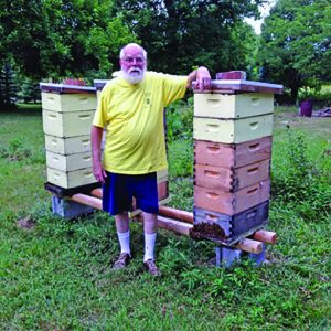 Editor Kim with some of his eight-frame hives. With one exception, all mediums.