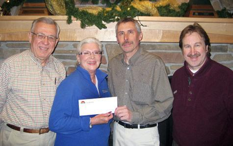 Jack and Betty Thomas of Paws and Claws Animal Shelter (from left) receive a check from Terry Hanson and Paul Maki of Nor-Son Construction.