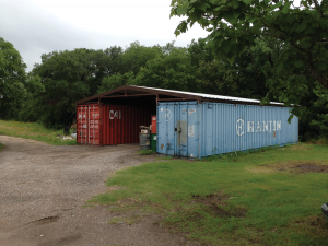 A unique outdoor storage area – two shipping containers and a roof between them.