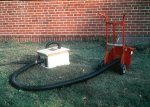 The 1976 model vacuum device. The smaller vacuum line entering on the top empties into a screened package bee cage.